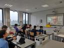 Een docent geeft via een videoverbinding vanuit huis les aan leerlingen in het klaslokaal.