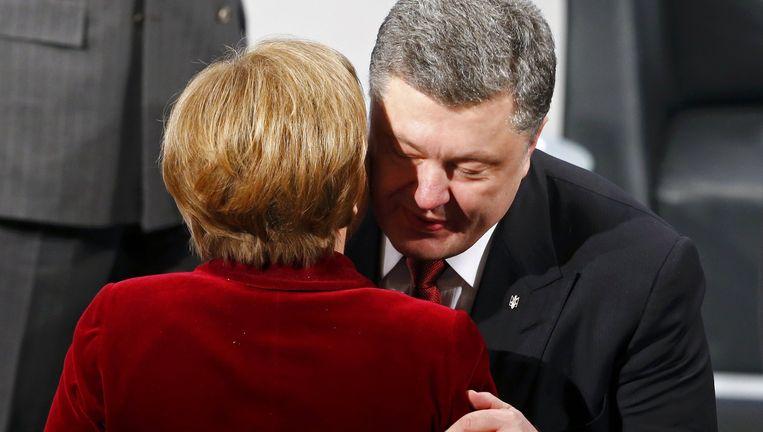 Merkel begroet de Oekraïense president Porosjenko tijdens de veiligheidsconferentie in München. Beeld reuters