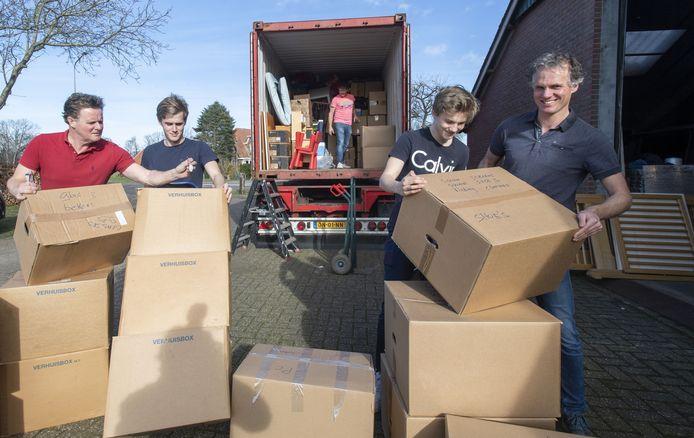 Brian Wegdam met zijn zoon Kris (rechts) en Raymond Wegdam met zoon Stan (links). Ze pakken hulpgoederen in een container die naar Sierra Leone gaat.