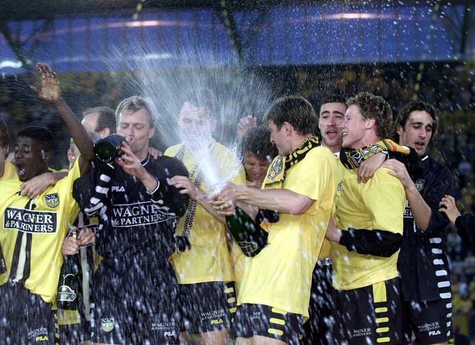 Frank Broers spuit met champagne nadat NAC in 2000 kampioen geworden is.