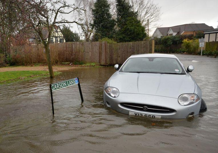 Een auto in Wraysbury, Berkshire.<br /><br />De Engelse overheid waarschuwt voor ernstig overstromingsgevaar in 14 plaatsen langs de de rivier de Theems. Duizenden huishoudens moeten zich daar op voorbereiden. Sinds december zijn al zo'n 8000 woningen getroffen door het hoge water.<br /><br />Ondanks alle maatregelen is vanmiddag het dorp Datchet ook ondergelopen.<br /><br />Na twee maanden van recordneerslag voorspellen meteorologen nog zeker tot en met donderdag iedere dag regen. Vooral de graafschappen Berkshire en Surrey zullen vermoedelijk met wateroverlast te maken krijgen. <br /><br />De Britten worstelen met het natste weer sinds 1766. Het water in de rivier stond in tientallen jaren niet zo hoog en stijgt nog steeds. Beeld afp