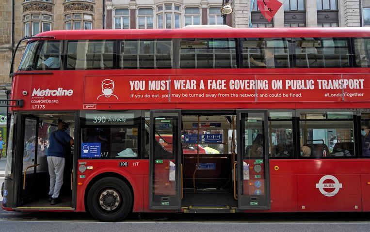 Een bus in Londen waarop wordt gewaarschuwd een mondmasker te dragen in het openbaar vervoer.  Beeld AFP
