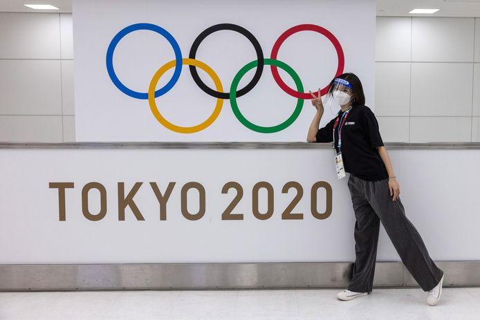 Een vrouw poseert bij het logo van de Olympische Spelen.