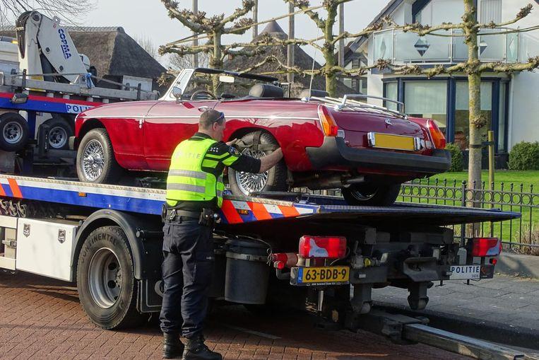 Een bij een onderzoek naar fraude in beslag genomen klassieke auto wordt afgevoerd Beeld Gerrit-Jan Ek