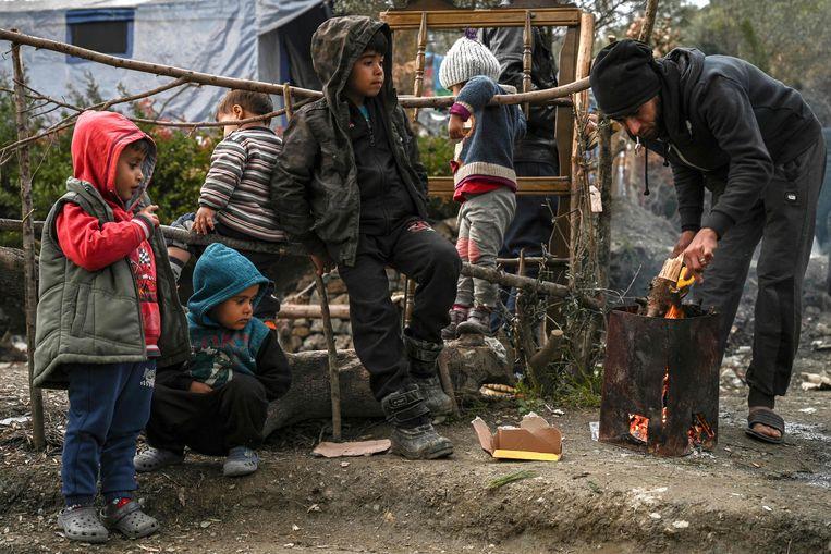 Migranten proberen zich warm te houden op het Griekse eiland Samos.  Beeld AFP