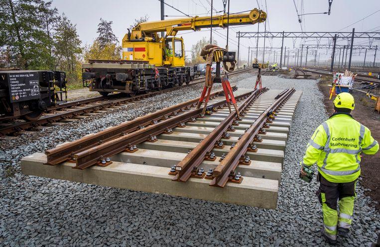 Werknemers werken aan een wissel op het spoor bij Hoofddorp.  Beeld Hollandse Hoogte /  ANP