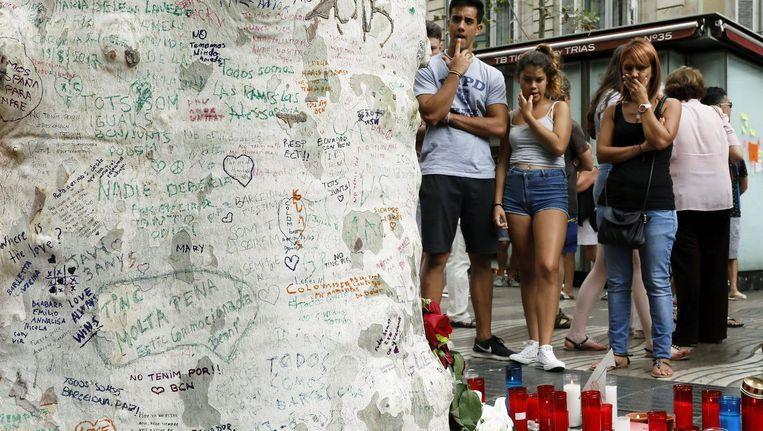 Mensen hebben op een boom op de Ramblas, de plaats van de aanslag, berichten geschreven om de slachtoffers te herdenken. Beeld epa