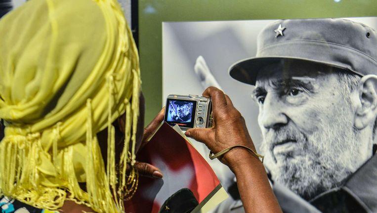 Een vrouw neemt een foto van een portret van Fidel Castro. Beeld afp