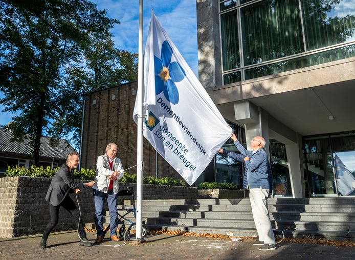De vlag wordt gehesen bij het gemeentehuis in Son en Breugel als teken van dementievriendelijke gemeente. Vlnr: Wethouder Paul van Liempd, Sjef den Uijl en Ad van den Hurk.