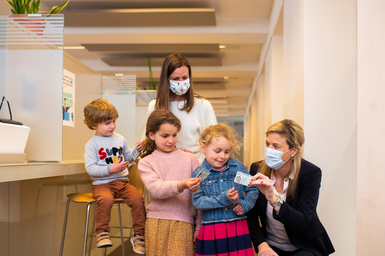 Annelies Verlinden overhandigt de vernieuwde Kids-ID's aan Felix (2), Emilia (8) en Roxanne (6)