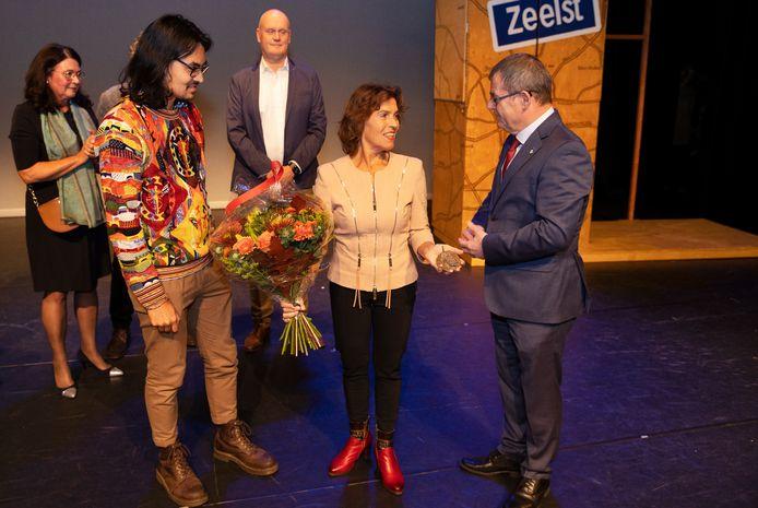 De vrouw en zoon van de vorig jaar overleden Arie den Braber nemen de Veldhovense Cultuurprijs namens hem postuum in ontvangst. Wethouder Hans van de Looij reikte de prijs uit in theater De Schalm.