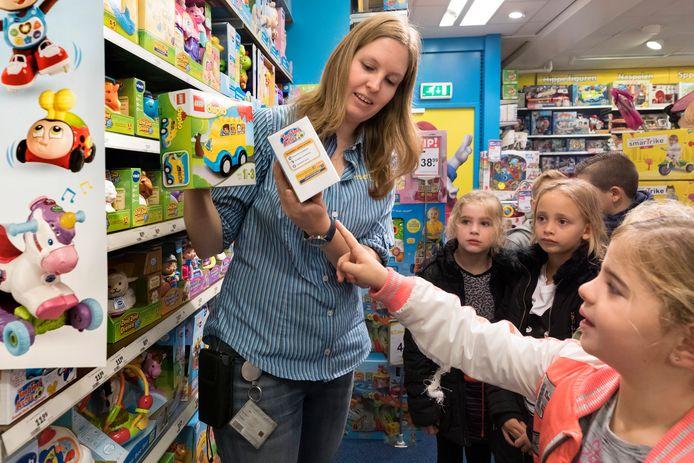 Medewerkster Reneé Groot leert de kinderen van de Wijboom wat ze af kunnen lezen aan de verpakkingen in de speelgoedwinkel.