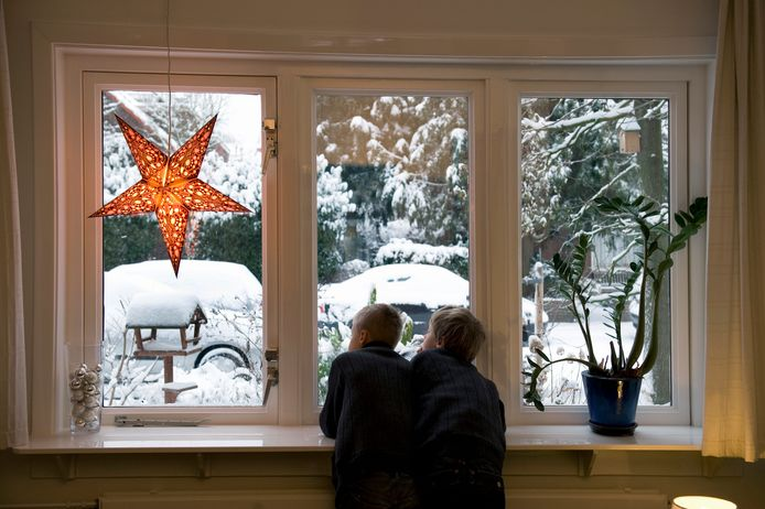 Twee jongetjes kijken met Kerstmis naar buiten naar de besneeuwde straat. In 2010 kenden we de laatste witte kerst.
