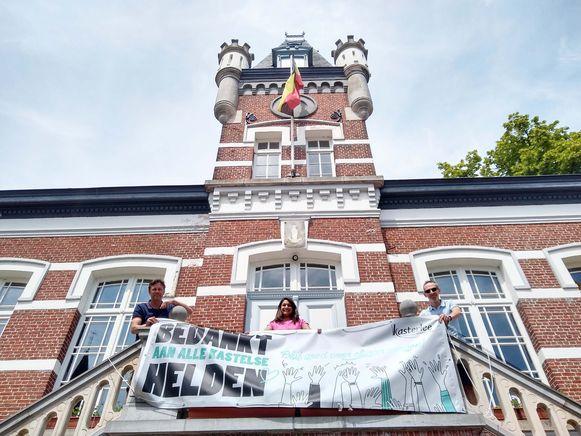 Schepenen Guy Van de Perre, Sumati Adriaensen en Gert Storms hangen het spandoek op aan het Erfgoedhuis in Tielen.