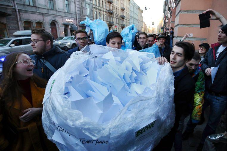 Actievoerders in Sint-Petersburg leveren een zak met papieren vliegtuigjes af na een gerechtelijke uitspraak in 2018 waarbij chatapp Telegram werd verboden nadat het weigerde versleutelde berichten te delen met de Russische veiligheidsdiensten. Beeld Peter Kovalev/TASS