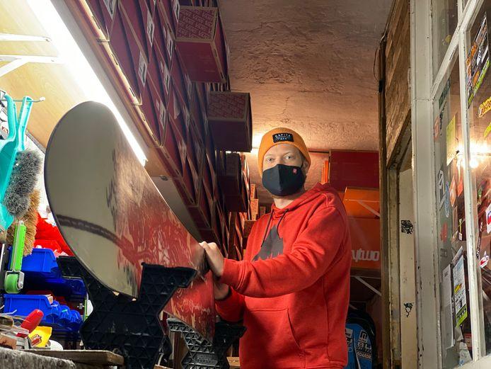 Verkoper Dimitri Van de Sande is een snowboard aan het waxen. West-Site is één van de weinige winkels waar het onderhoud nog met de hand gebeurt.