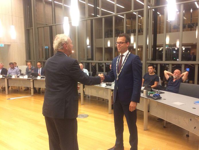 Herman Klitsie feliciteert Derk Alssema nadat hij hem de ambtsketen heeft omgehangen.