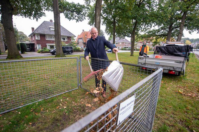 Wethouder Jan Martin van Rees gooit eikenbladeren van de bomen aan de Vissedijk in de eerste van in totaal zeventig bladkorven die de gemeente Almelo gaat plaatsen.