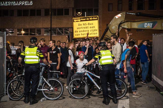 Voor het station moeten veel mensen wachten, de politie blokkeert de route naar het station.