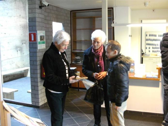 Jelmer overhandigt het schriftje van Rina Groeneveld (midden) aan Annie Ponsioen.