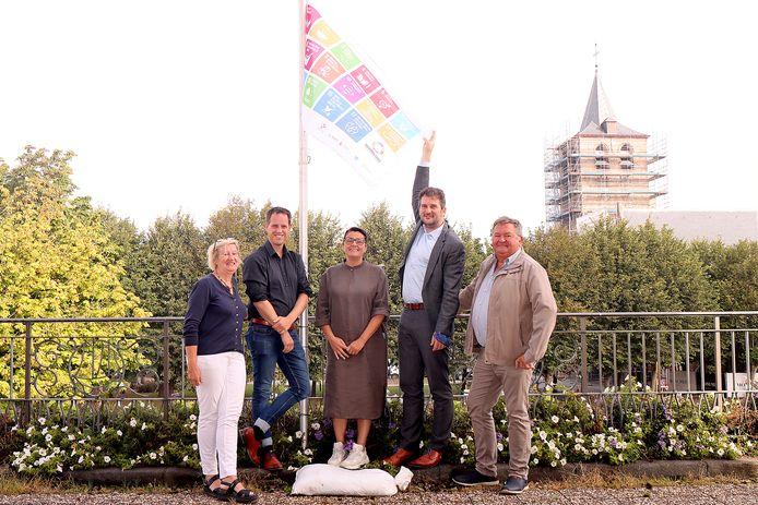 Een deel van het gemeentecollege bij de vlag van de duurzaamheid