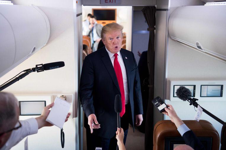 Donald Trump spreekt met de pers aan boord van de Air Force One.  Beeld AFP