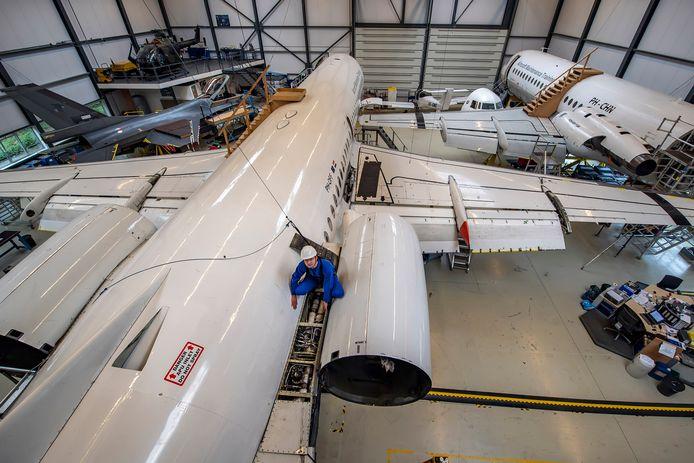 Curio-student vliegtuigtechniek Jelle Hauet aan het werk aan een Fokker 100 bij Aviolanda in Hoogerheide. Links staan een F16 en een Bölkow-helikopter, rechts een Fokker F28.