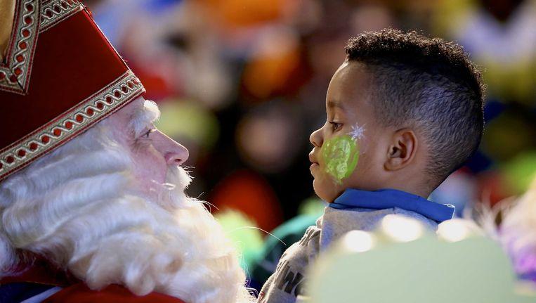 Sinterklaas begroet een kind in het Spoorwegmuseum tijdens een sinterklaasfeest met kinderen uit opvangcentra. Beeld ANP Kippa