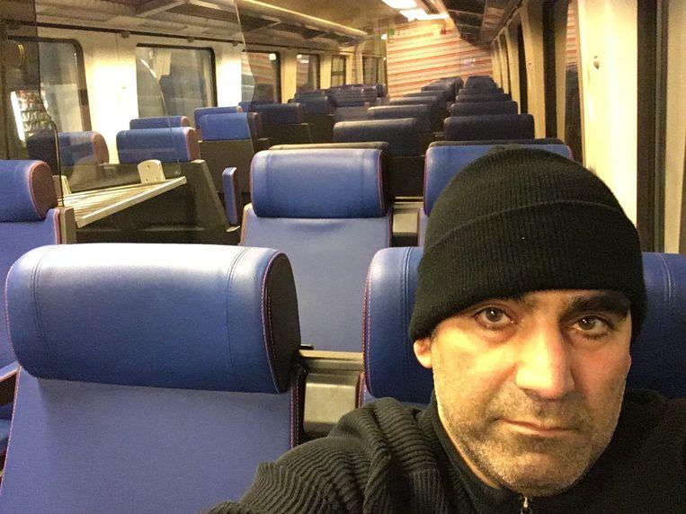 Journalist Bahram Sadeghi op de trein van Amsterdam naar Brussel. Beeld RV