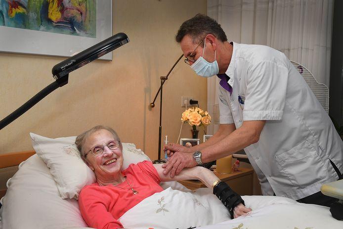Riet Blom krijgt van verpleegkundige Wim Berendijk als een van de eerste bewoners van Sint Anna in Boxmeer een spuit tegen het coronavirus.