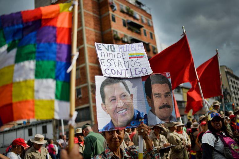 Bij een demonstratie in Venezuela toont iemand de tekst 'Evo. Volk. Vriend. We zijn met jou', samen met portretten van oud- en huidig Venezolaans president Chavez (l.) en Maduro (r.).  Beeld AP