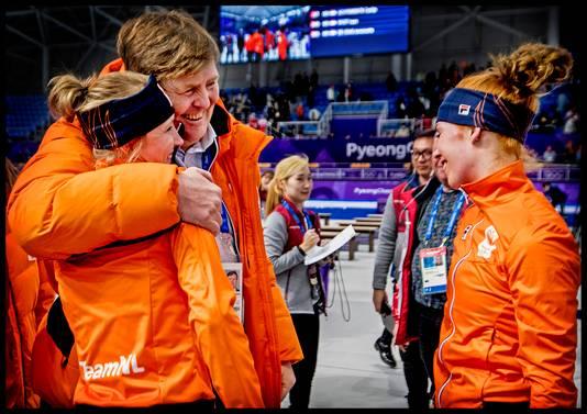 Koning Willem-Alexander legt zijn arm om de schouder van winnares Carlijn Achtereekte.
