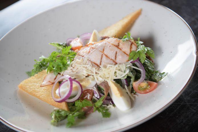 Caesarsalade van Romeinse sla, olijven, Parmezaanse kaas, croutons en gegrilde kip met een ansjovisdressing.