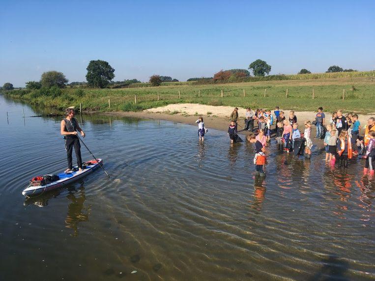 Plastic Soup Surfer Merijn Tinga ontmoet op de Maasover kinderen van een basisschool voor de actie Wakkere Wegwerpers. Beeld Botsmedia