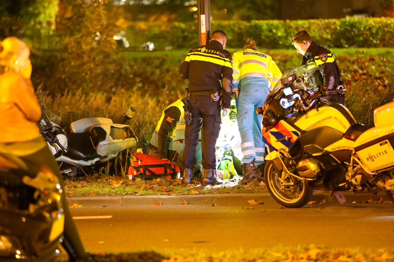 Ambulancepersoneel verleent eerste hulp aan de aangereden motoragent.