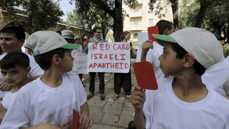 Palestijnse kinderen houden uit protest een rode kaart op tijdens de komst van Sepp Blatter aan Jeruzalem. Beeld reuters