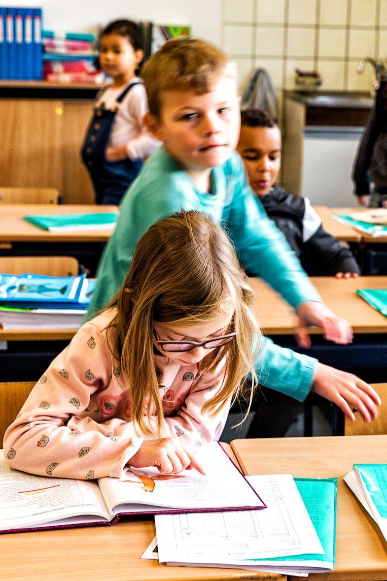 ► Veel leerlingen in het lager onderwijs leren nog altijd lezen met de chronometer onder tafel. Beeld Hollandse Hoogte / marlieswessels.nl