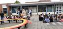 Directeur Robin Regelink (met papier en lichtblauw overhemd) opent de Middelburgse zomerschool officieel met het bekendmaken van het 'leerthema' voor de komende weken: water. Half verscholen achter hem Archipelbestuurder Henk Zielstra en wethouder Carla Doorn.