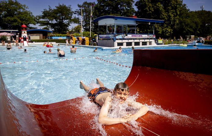 Zwemmers zoeken verkoeling in een openluchtzwembad tijdens een van de tropisch warme dagen in juni dit jaar.