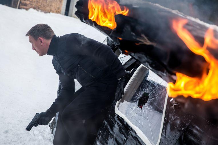 Bond (Daniel Craig) worstelt zich uit een brandend vliegtuig in Spectre. Beeld