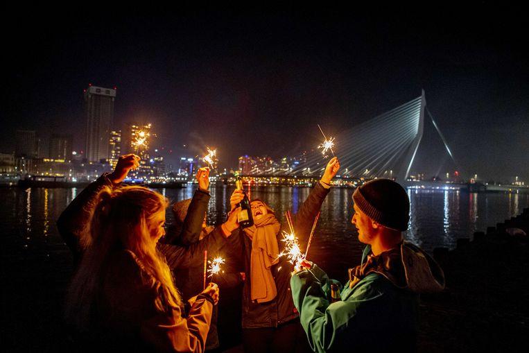 In Rotterdam proosten mensen met sterretjes bij de Erasmusbrug, die dit jaar niet zoals gewoonlijk is verlicht door een vuurwerkspektakel.  Beeld ANP