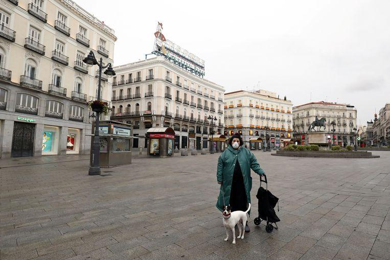 Sara, 35 poseert met haar hond Jueves in het vrijwel lege Puerta del Sol.  Zij mag haar hond uitlaten.  Beeld REUTERS/Sergio Perez