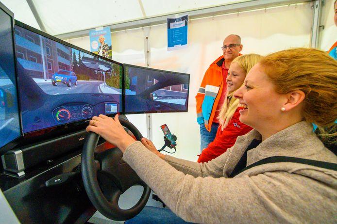 Barbara Edens en haar dochter Annemarijn kijken aandachtig naar de schermen van de simulatie van Veilig Verkeer Nederland op de Septembermarkt in Harmelen