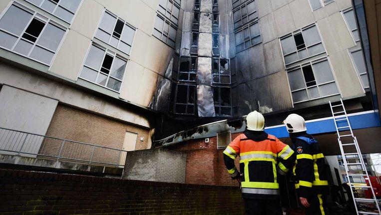 Brandweerlieden bekijken de schade aan wooncentrum De Notenhout, die ontstaan is vanwege een brand. Beeld anp