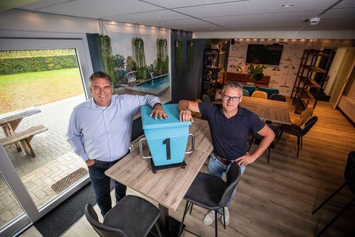 Bestuurslid Hardy Bruins (links) en 'bouwpastoor' Rob Velthuis leunen in het vernieuwde clubhuis op een startblok van het oude binnenbad. Op de achtergrond de chilhoek annex hangplek voor de jeugd.