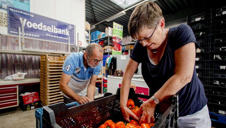 Vrijwilligers sorteren paprika's bij de voedselbank in Maassluis. Het CDA wil dat van vitale ouderen en werklozen mag worden gevraagd een aantal uren per week vrijwilligerswerk te doen. Beeld ANP