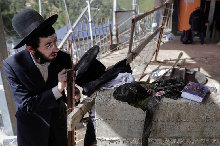 Een orthodox-joodse man bekijkt spullen die zijn gevonden op de plaats van de ramp. Beeld AP