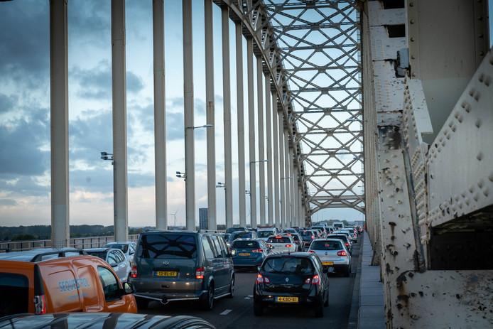 File op de Waalbrug in Nijmegen. De e-bike moet gestimuleerd worden, zegt professor Mobiliteit van de Radboud Universiteit Henk Meurs, zodat mensen die binnen een straal van 10 kilometer van hun werk wonen, niet meer met de auto gaan maar met de fiets.