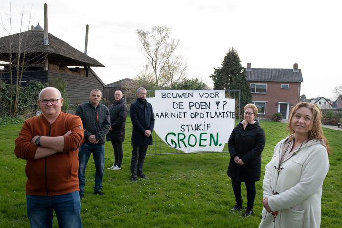 Piet Schimmel (linksvoor) en zijn vrouw Erica (eerste van rechts) met andere buurtbewoners op de bedreigde groenstrook in Kerk-Avezaath. Op de achtergrond is hun woning te zien.