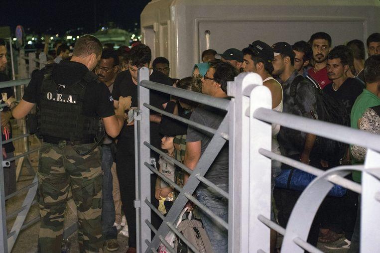 Syrische vluchtelingen wachten om aan boord te mogen gaan van het cruiseschip Eleftherios Venizelos, een tijdelijke verblijfplaats voor asielzoekers. Beeld EPA
